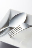 Fork And Spoon. With white plate closeup Royalty Free Stock Images