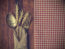 Fork and spoon with the ears of wheat. Vintage toned picture of the fork and spoon with the ears of wheat lying at the old table Stock Photos