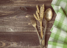Fork and spoon with the ears of wheat. Vintage toned picture of the fork and spoon with the ears of wheat lying at the old table Stock Photography