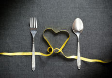 Fork and spoon with heart shape made from yellow ribbon on black. Textured background sample Royalty Free Stock Images