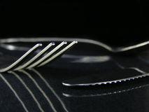 Fork, spoon, and knife. On a isolated reflective black baackground royalty free stock image