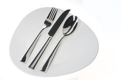 Fork, spoon and  knife on a plate over white Royalty Free Stock Image