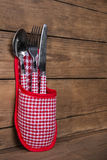 Fork, spoon and knife in red white checked colors on wooden back Stock Photos