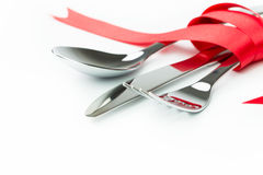 Fork, spoon and knife tied up with red ribbon Stock Photos