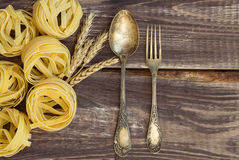 Fork and spoon with pasta and the ears of wheat. Ancient fork and spoon laying at the old table with pasta and ears of wheat Royalty Free Stock Photography