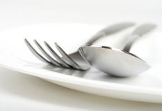 Fork and spoon on plate Royalty Free Stock Photo