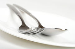 Fork and spoon on plate Royalty Free Stock Image