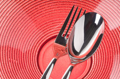 Fork and spoon on red plate Stock Photos