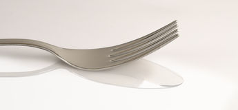 Fork on spoon reflection. On white background royalty free stock photos