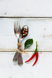 Fork and spoon. Spices, red hot chili peppers with vintage fork and spoon on white wooden background. Top view Royalty Free Stock Image
