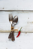 Fork and spoon. Vintage fork and spoon on white wooden background with one red hot chili pepper. Top view Stock Images