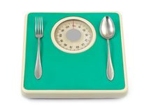 Fork and spoon on weight scale Royalty Free Stock Photography