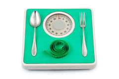 Fork and spoon on weight scale Royalty Free Stock Photos