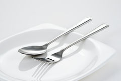 Fork & Spoon on white dish. Fork and Spoon on white dish stock photos