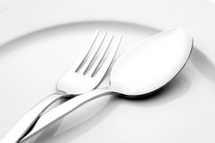 Fork and spoon on white plate. Detail of fork and spoon on white plate Royalty Free Stock Photography