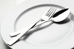 Fork and spoon on white plate. Detail of fork and spoon on white plate Stock Image