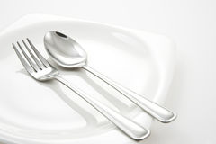 Fork and Spoon on white plate Royalty Free Stock Photo