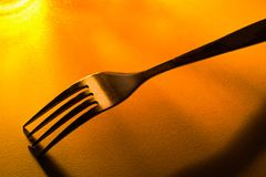 Fork on the table with yellow, contrast light. Fork with yellow, contrast light Royalty Free Stock Photos