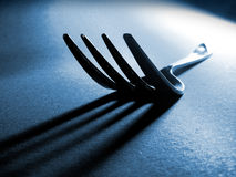Fork tines and shadow. On textured surface Royalty Free Stock Images
