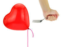 Fork about to pop a heart balloon. Isolated on white royalty free stock photography