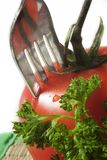 Fork and tomato. Fork put into in to tomato and parsley, close up Royalty Free Stock Photo