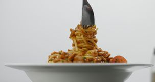 Eating spagetti bolognese with a fork. Fork twisting in succulent hot spaghetti bolognese with chives isolated on white stock video