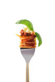 Fork whit spaghetti bolognese. Fork whit snack: spaghetti bolognese whit fresh garlic and basil Stock Photography