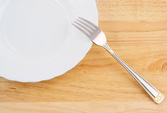 Fork and white plate Royalty Free Stock Image
