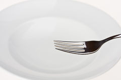 Fork on a white plate Royalty Free Stock Images
