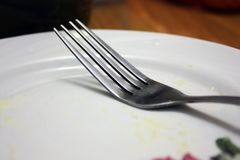 Fork on a white plate stock photos