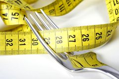Fork wrapped in measure tape in diet and overweight concept Royalty Free Stock Photography