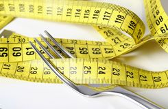 Fork wrapped in measure tape in diet and overweight concept Royalty Free Stock Image