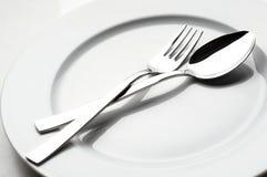 Fork y cuchara en la placa blanca Imagen de archivo