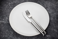 Fork y cuchillo en la placa blanca Imagenes de archivo