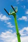 Forkes hidráulicas telescópicas verdes con el cielo azul Imagen de archivo
