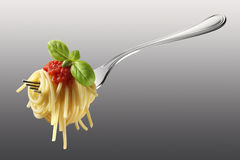 Forkful of spaghetti with tomato sauce and basil. Appetizing spaghetti rolled on fork with typical Italian sauce Stock Image