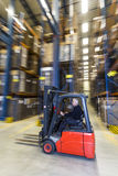 Forklif driving trough a warehouse Stock Photography