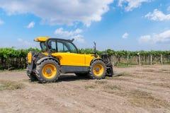 Forklift φορτωτής του κίτρινου χρώματος σε έναν τομέα σε ένα υπόβαθρο αμπελώνων στοκ φωτογραφία με δικαίωμα ελεύθερης χρήσης