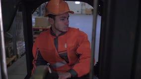 Forklift χειριστής στο σκληρό κράνος και ομοιόμορφη αποθήκη εμπορευμάτων γύρου μέσω των σειρών των ραφιών αποθήκευσης με τα εμπορ απόθεμα βίντεο