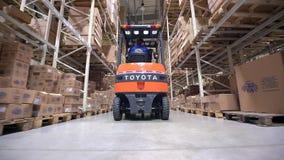Forklift η κίνηση φορτηγών μεταξύ των μεγάλων ραφιών μετάλλων σε μια σύγχρονη αποθήκη εμπορευμάτων και ξεφορτώνει τις παλέτες με  Στοκ φωτογραφία με δικαίωμα ελεύθερης χρήσης