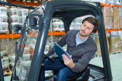 Forklift οδηγός που εξετάζει την περιοχή αποκομμάτων στην αποθήκη εμπορευμάτων στοκ εικόνα