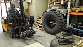 Forklift οδηγός προστατευτικό οδηγώντας forklift φανέλλων στην αποθήκη εμπορευμάτων του φορτίου που διαβιβάζει την επιχείρηση Άτο στοκ φωτογραφία
