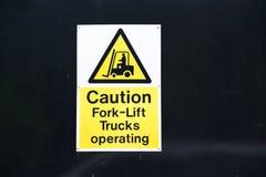 Forklift φορτηγά που ενεργοποιούν το σημάδι προσοχής κίτρινο και άσπρο στο μαύρο υπόβαθρο στοκ εικόνες