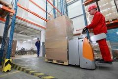 Forklift φορτωτής με το φορτίο χαρτονιού που κινείται στην αποθήκη Στοκ Εικόνες