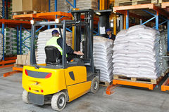Forklift. Driver handling goods in distribution warehouse royalty free stock photography