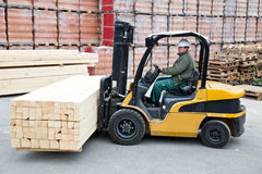 Forklift. Operator lifting bunch of wood stock images