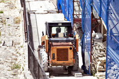 Forklift on a building site next to renovated house with scaffolding Royalty Free Stock Photography