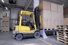 Forklift with carton boxes in factory. Yellow forklift with carton boxes in factory Stock Image