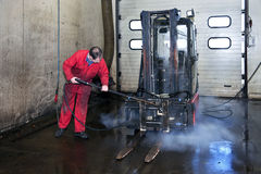 Forklift cleaning. Man cleaning a forklift using a high pressure spray gun with hot, steaming, water stock photo