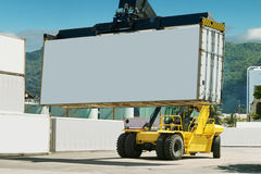 Forklift and container port. Forklift is loading cargo containers in the dock. The white board of container is close-up & free for your text Stock Image